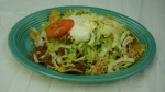 Nachos Supreme - Cheese nachos topped with chicken, beef and beans. Covered with lettuce, tomatoes and sour cream.